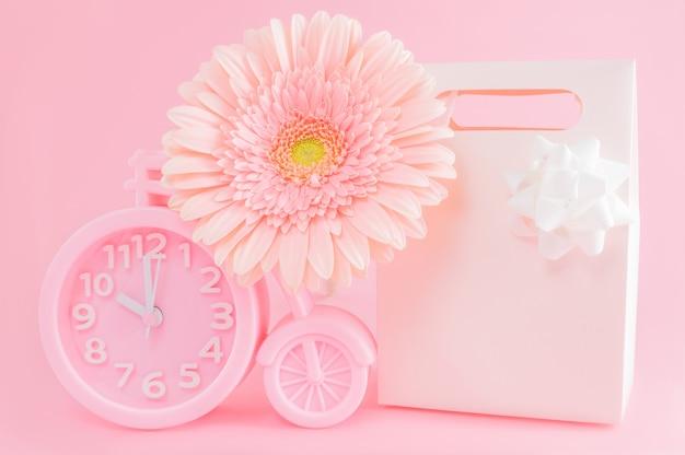 Розовый будильник, подарочная коробка и цветок герберы