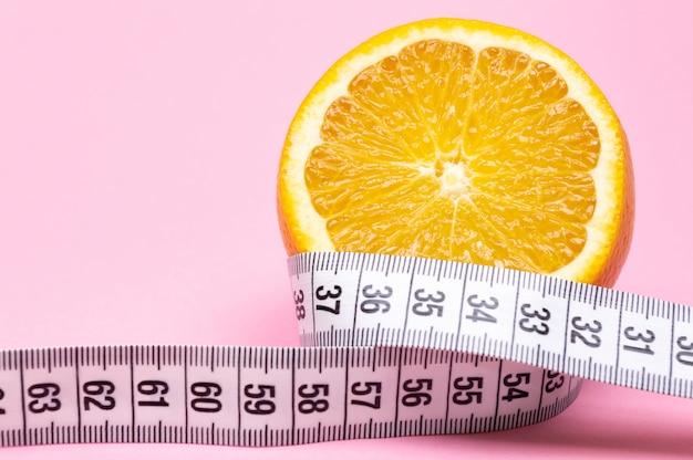 Нарезанный апельсин и измерительная лента на розовом фоне. концепция диеты.