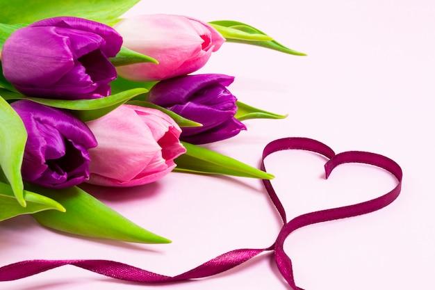 紫色のリボンと明るいピンク色の背景に紫とピンクのチューリップの花束で作られたハート形