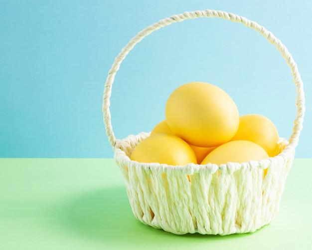 Красочные пасхальные яйца в белой корзине. цветной фон