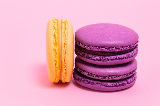 Три цветные миндальное печенье на розовом фоне.