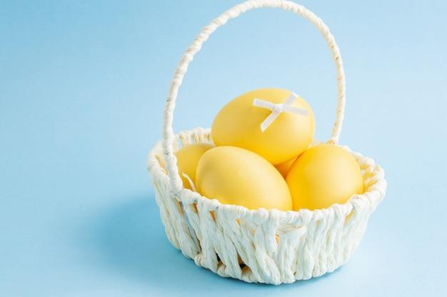 Красочные пасхальные яйца в белой корзине на синем фоне.