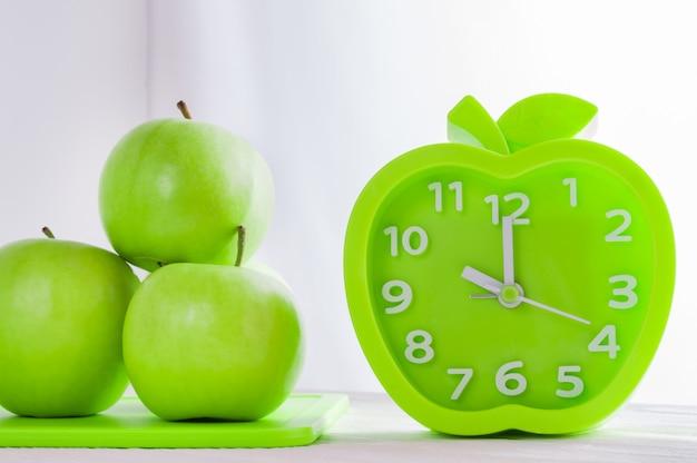 Будильник и зеленые яблоки на белом деревянном столе. доброе утро, здоровое утро или диета концепции.