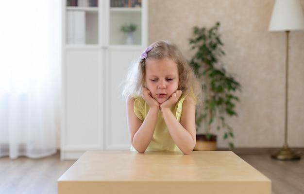 悲しい少女はテーブルに座って見下ろしています