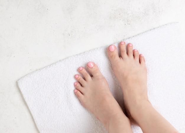 美しいピンクのペディキュアで女性の足