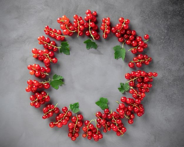 緑の葉と新鮮な赤スグリのフードフレーム