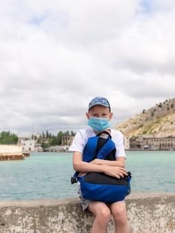 Мальчик-подросток в защитной маске и держит рюкзак