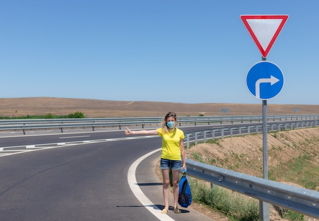 Женщина в защитной маске на дороге
