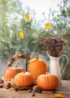 カボチャ、ナッツ、黄色の葉、ウィンドウにドライフラワーの花束の美しい秋の静物