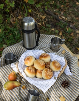 屋外のピクニック。ティーコーヒー、おいしいパンと魔法瓶