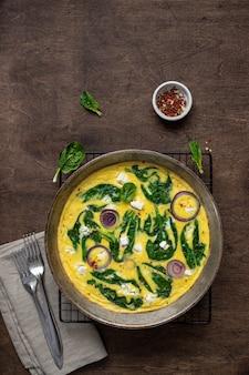 Домашний, вкусный омлет или фриттата со шпинатом, сыром фета, красным луком в железной сковороде на деревенском столе. вид сверху