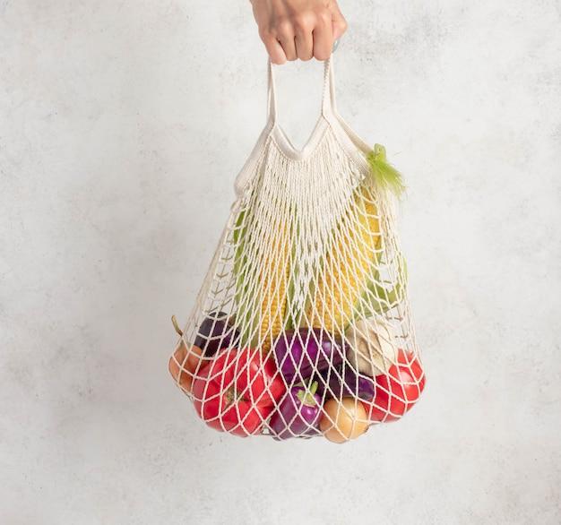 女性の手を握っている野菜のメッシュバッグ。