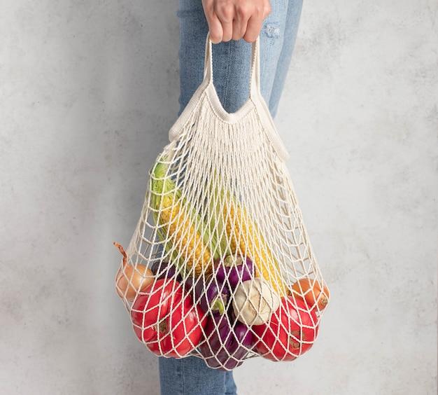 新鮮な野菜のメッシュバッグを保持している若い女性。