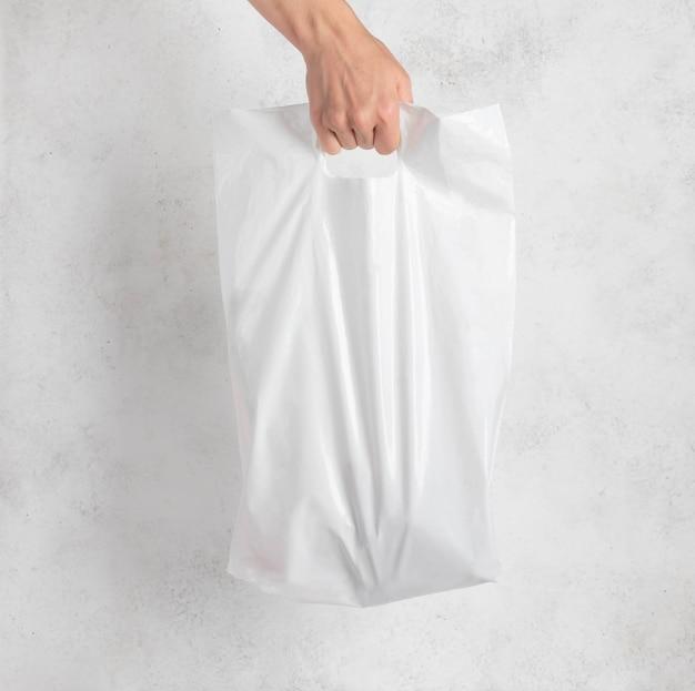 女性の手で持った白いビニール袋