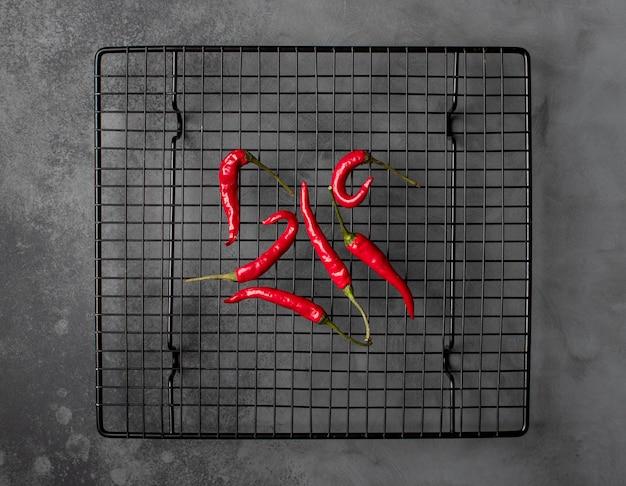 Красный острый перец чили на металлическом гриле