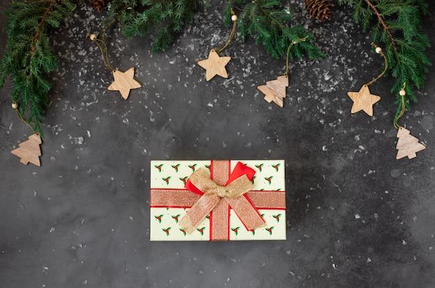 クリスマスツリーの枝と赤いリボンのギフトボックス。