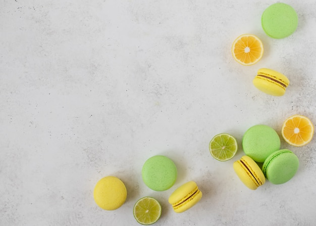 マカロンとレモン、ライムのスライス。白いコンクリートの背景。コピースペース