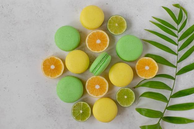 黄色と緑のマカロン、レモンのスライス、ライムホワイトのコンクリート表面
