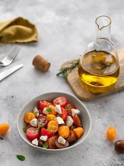 Салат из свежих овощей с сыром фета в миске здоровая пища диета серая бетонная поверхность,
