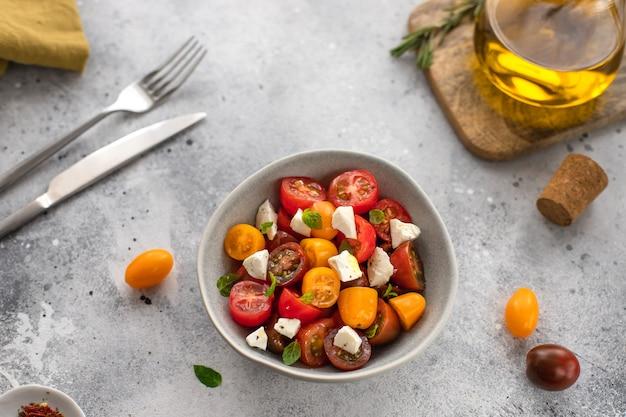 Салат из свежих красочных помидоров черри, базилика и оливкового масла серой поверхности