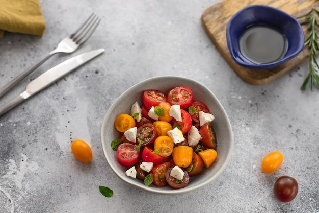Салат из свежих овощей с сыром фета в миске здоровая пища с большим количеством витаминов серая бетонная поверхность