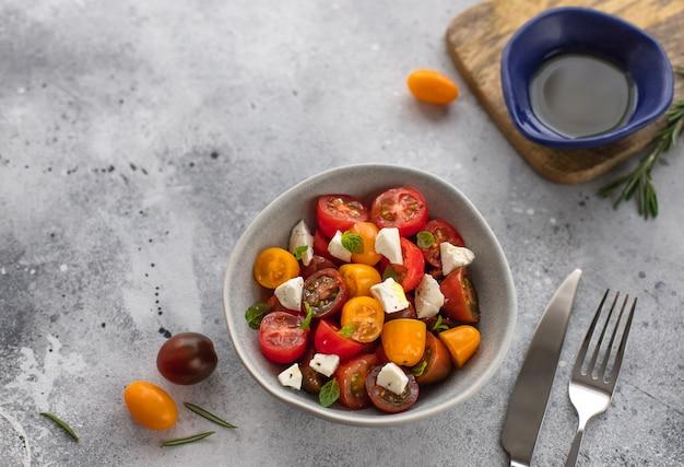 Диетический салат со свежими помидорами черри, сыром фета, розмарином и оливковым маслом вегетарианская здоровая концепция серая бетонная поверхность,
