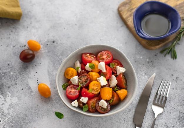 Салат с красочными помидорами черри, сыром фета, зеленью, оливковым маслом средиземноморской кухни с серой бетонной поверхностью,
