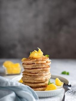 オレンジとミントグレーの表面で飾られた全粒粉パンケーキのスタック、