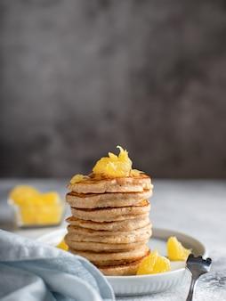 全粒粉パンケーキにオレンジ色の健康食品コンセプトグレーの表面を添えて、