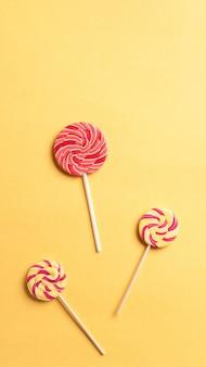 Полосатый спираль разноцветные леденцы на желтом фоне. сладкий десерт школьная закуска. вертикальное изображение. копировать пространство