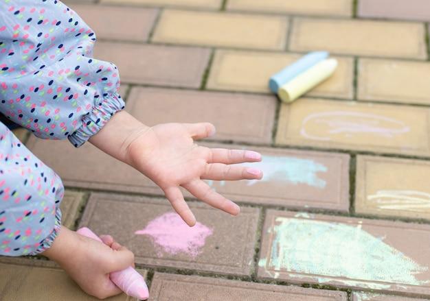 ピンクのチョークで染色された子供の手のひら。歩道に描くチョーク。アート、子供向けの創造的な教育。ソフトフォーカス