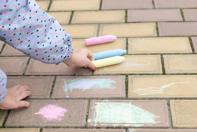 Маленькая девочка берет мел, чтобы рисовать на асфальте, тротуаре. уличное искусство, образование детей