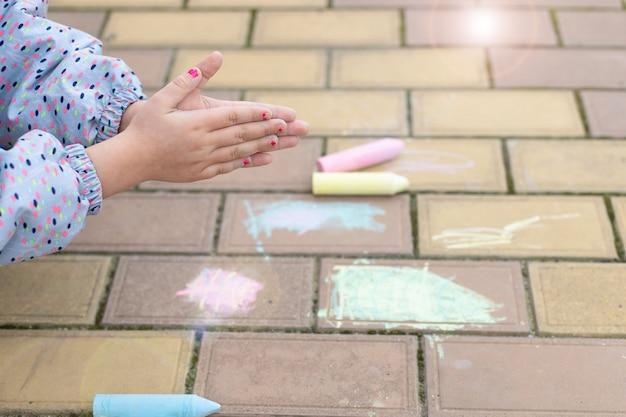 Маленькая девочка чистит грязные руки, после рисования мелом на тротуаре. мягкий фокус
