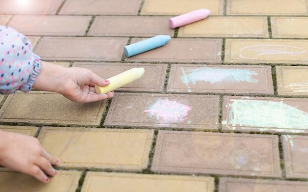 Маленькая девочка выбирает мел для рисования на асфальте, тротуаре. активные детские игры