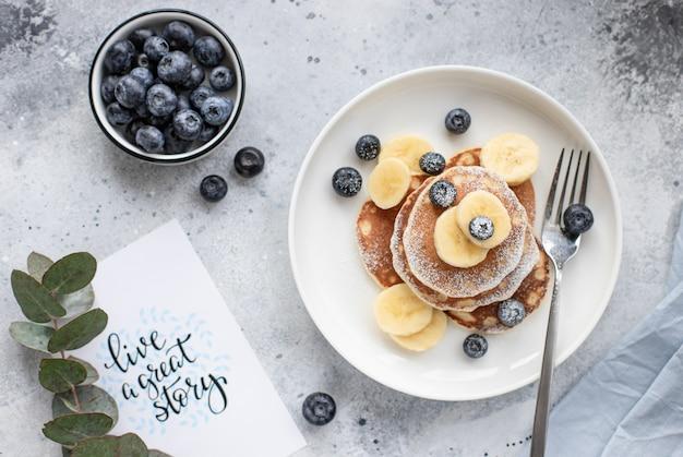 灰色の背景に新鮮なブルーベリー、バナナ、粉砂糖のパンケーキ。健康的な朝食用食品。水平方向の画像、平面図、平面レイアウト