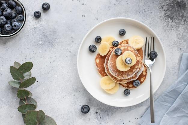 新鮮なブルーベリー、バナナ、灰色のコンクリート背景に粉砂糖とおいしいパンケーキ。水平方向の画像、上面図、テキストの配置