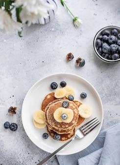 新鮮なブルーベリー、白い花と灰色の表面にバナナのパンケーキ。おいしい朝食。垂直方向の画像、上面図