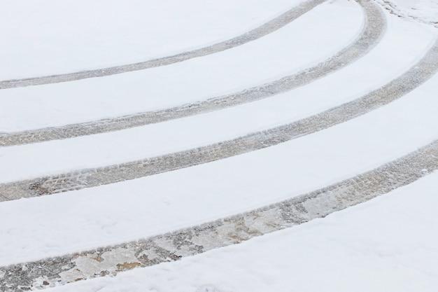 新雪のカーブしたタイヤ跡。道路上の氷。