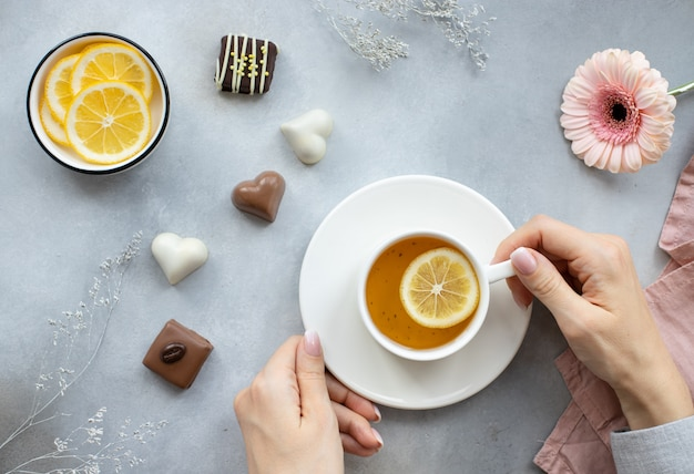 Руки женщины, держа чашку горячего чая с лимоном и различные сладости на серой поверхности с цветами.