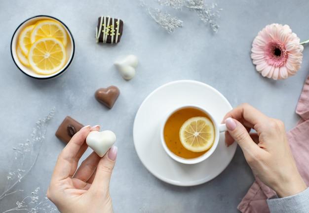 Руки женщины, держа белые шоколадные конфеты в форме сердца и чашку чая на серой поверхности с цветами.
