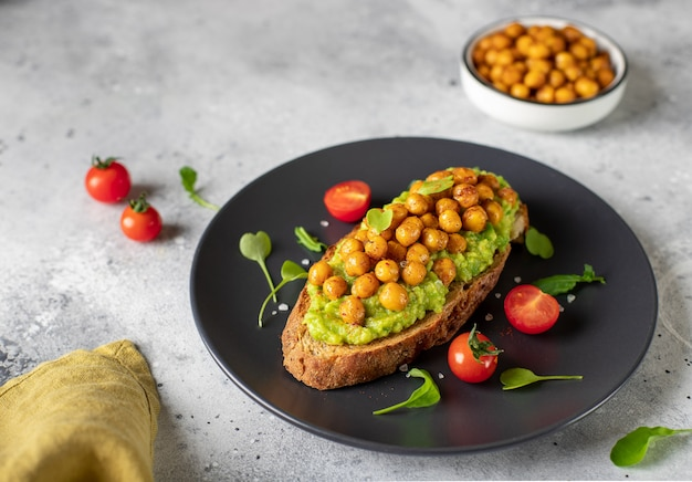 Закваска ржаного хлеба тост с авокадо, жареный нут на темной тарелке. вкусная и полезная веганская еда. серая поверхность, горизонтальное изображение