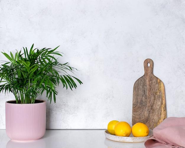Комнатное растение в вазоне, лимоны и разделочная доска на кухонном столе. домашнее цветоводство.