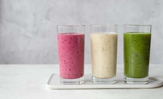 Ассортимент фруктовых и овощных смузи в бокалах на сером