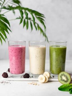Три различных фиолетовых, желтых, зеленых коктейля с ингредиентами. здоровый завтрак детокс.