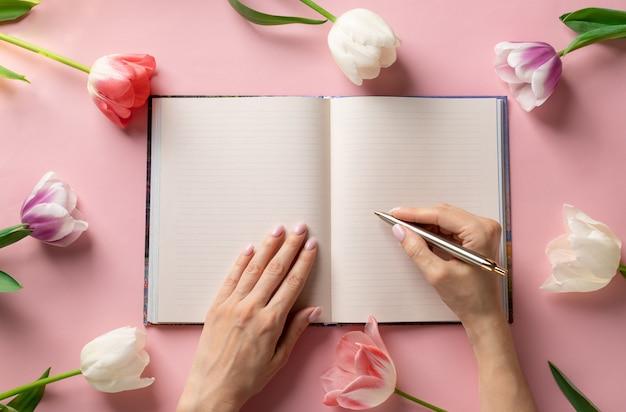 色とりどりのチューリップのフレームとピンクの背景に開いている空白のノートブックにペンで書く女性の手。ライフスタイルの穏やかな背景。