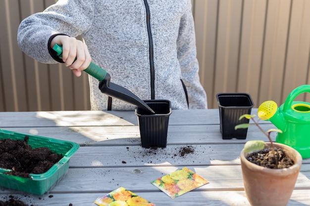 Мальчик кидает почву в рассаду горшки для посадки семян маленького садовника по горизонтали