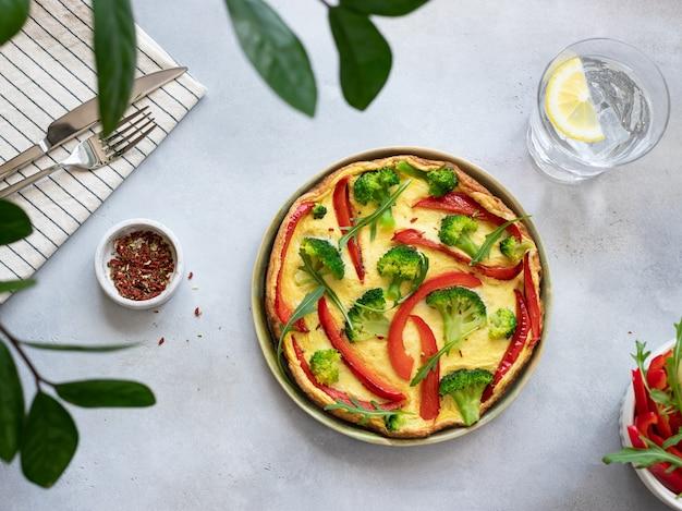 イタリアのフリッタータブロッコリー、ピーマン、ルッコラと灰色の石の背景においしい自家製の朝食、水平