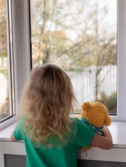 Блондинка держит плюшевого мишку и смотрит в окно на сад