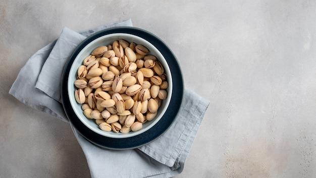Керамическая тарелка с фисташками на серую стену. здоровое питание