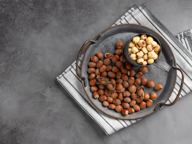 Взгляд сверху стерженей фундука и всего фундука в металлическом блюде на серой стене. органическая еда